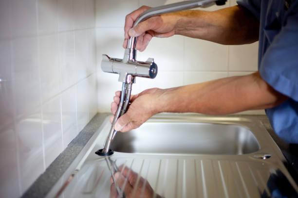 Gros plan sur les mains d'un plombier qui répare un robinet de cuisine